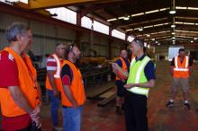 Ausplow product manager Gary Andrews talks with a group of DBS owners about the production flow at the start of the tour.