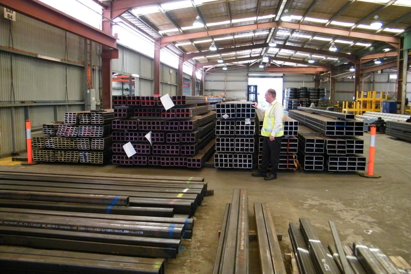 Ausplow general manager Chris Farmer checks over the latest delivery of steel at the company's Naval Base factory this week. An astute ordering move means there will be no price increases related to imminent price rises in steel.